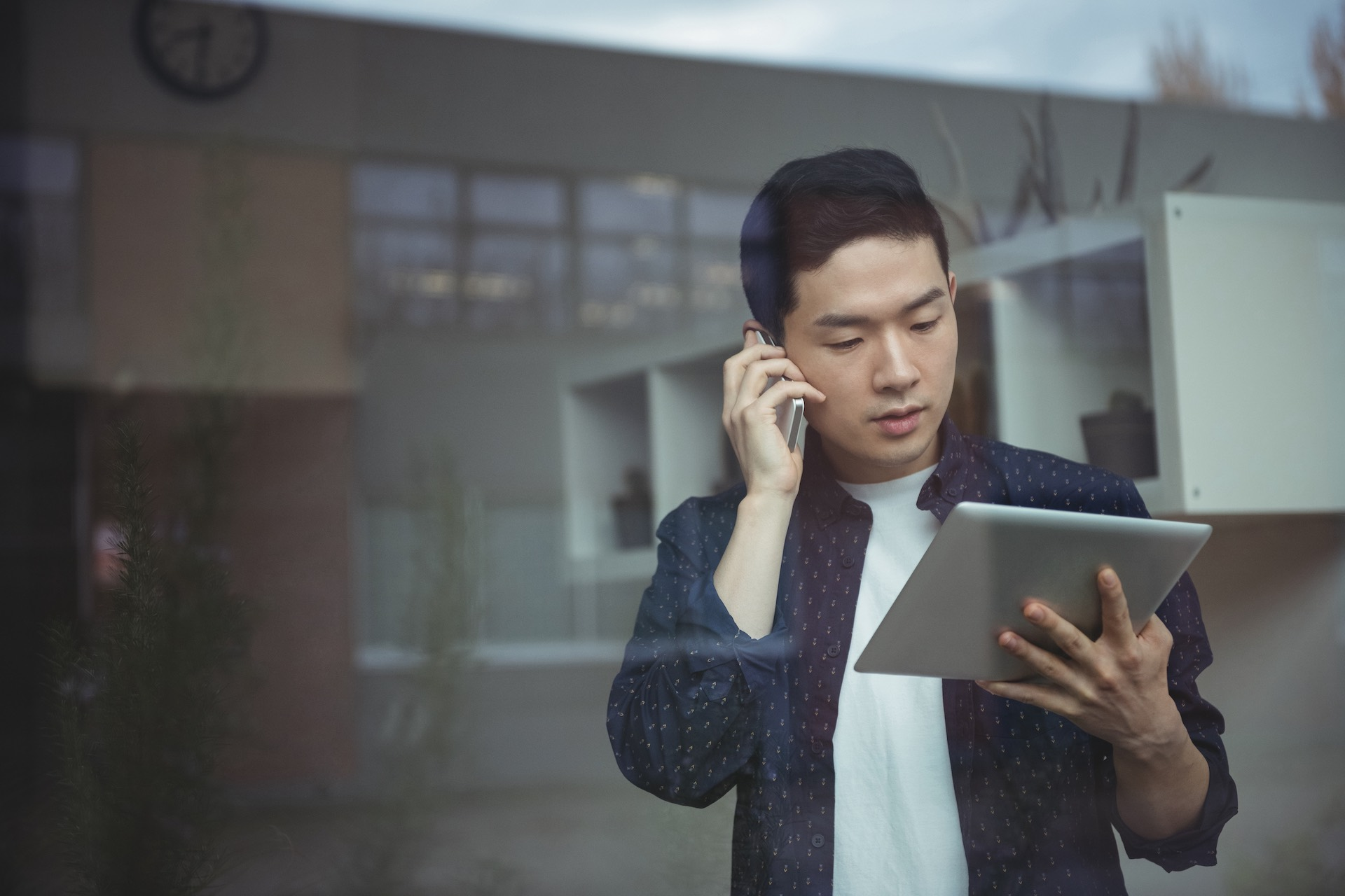 Business executive talking on mobile phone while using digital tablet in office